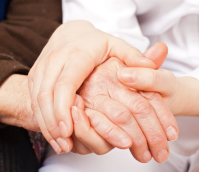 hands of an elderly woman and her caretaker holding together
