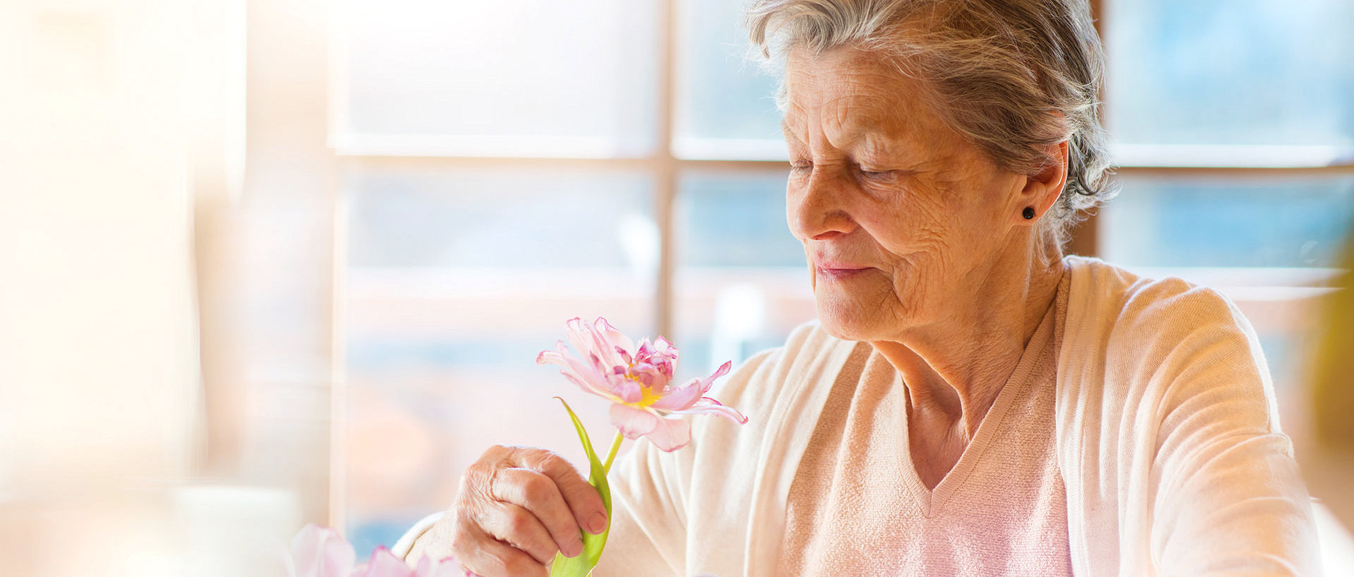 elderly woman holding a flower