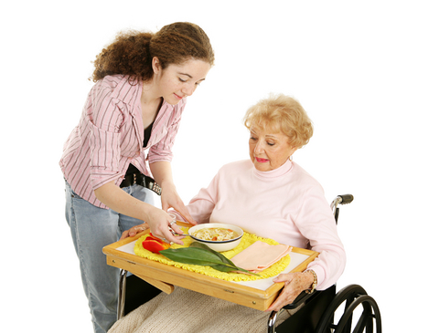 Caregiver assisting an elderly woman feed herself
