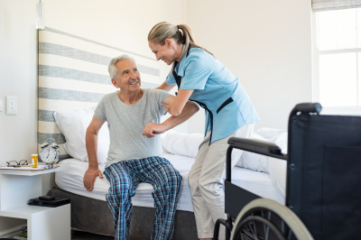 caregiver assisting senior man to get up from bed