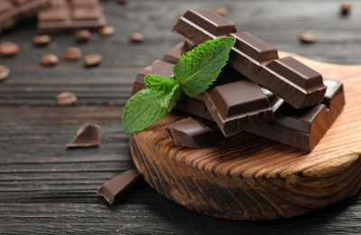 Pieces of dark chocolate with mint on wooden table
