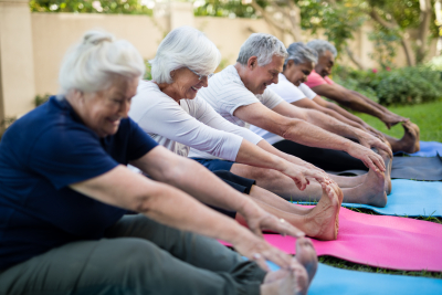 Smiling senior people doing stretching exercise while sitting on exercise mats