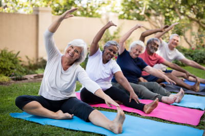 smiling senior friends exercising on mats