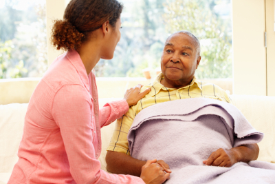 Woman looking after sick senior man