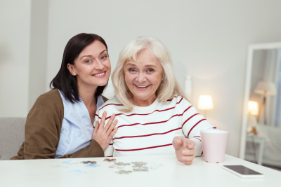 senior woman and caregiver looking at camera while gathering puzzle