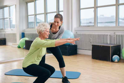 women doing exercise with her personal trainer at gym