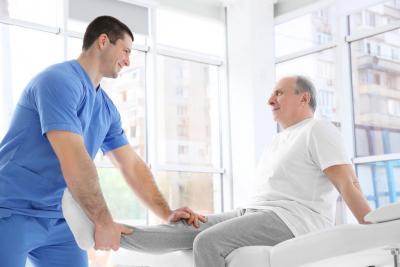 caregiver stretching the knee of senior man