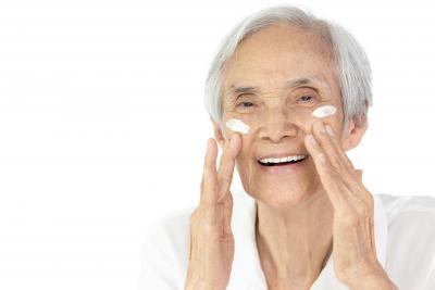 senior woman applying skin care
